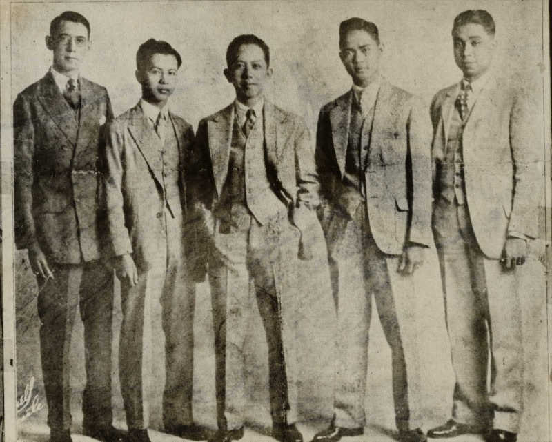 "Team members of the University of the Philippines debate team, with Professor Carlos P. Romulo (center). From left: Pedro Camus, Teodoro Evangelista, Deogracias Puyat, and Jacinto C. Borja. The photo was taken in San Francisco, California, April 18, 1928, and the caption reads: ""Four students of the University of the Philippines, under the leadership of Prof. Carlos P. Romulo of the College Faculty, recently arrived in the United States on a tour of the world to debate the question of Filipino independence. The round-the-world debate on the Philippine question is academic and has nothing to do with politics."""